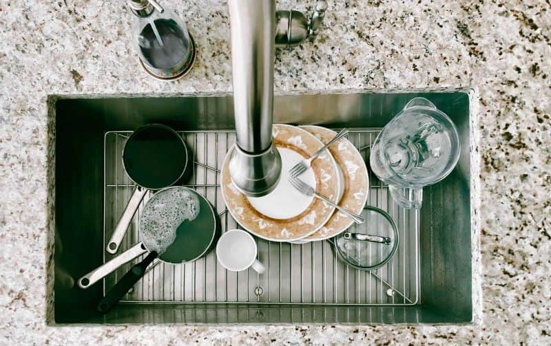 Dirty dishes sitting in a sink on a metal grid (Photo by Grace Cary/Moment via Getty Images)