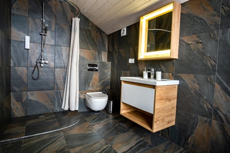 Bathroom with a doorless shower, wall-hung toilet, wood vanity and mirror, and black-and-brown tiles on the floor and walls (Photo by bilanol – stock.adobe.com)