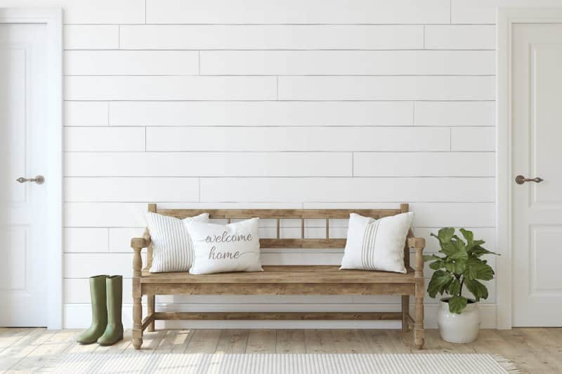 Entryway with boots, a plant and a wooden bench with throw pillows in front of a white shiplap accent wall between two doors (Photo by poligonchik - stock.adobe.com)