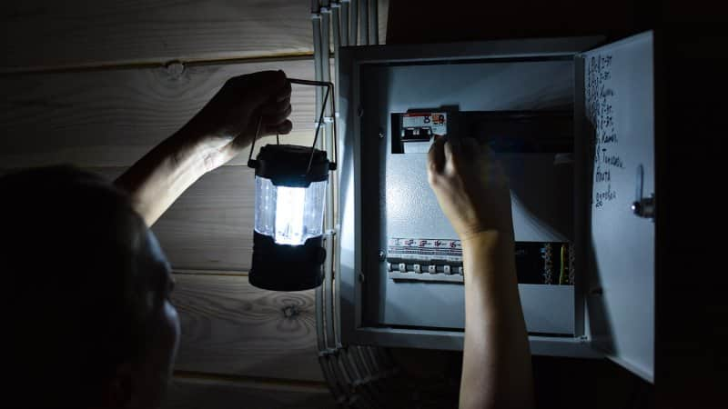 Looking at an electrical panel with flashlight (Photo by Victoria - stock.adobe.com)