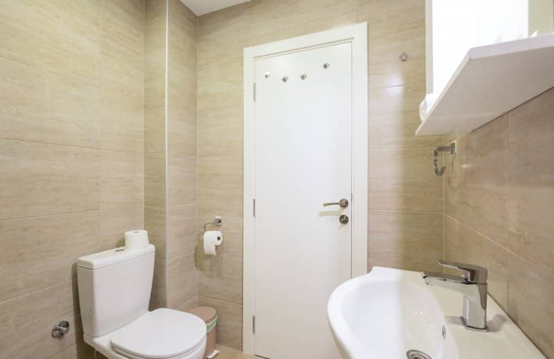 Small bathroom with floor to ceiling beige tiles (Photo by rilueda – stock.adobe.com)