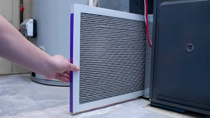 Person changing air filter on furnace (Photo by Marvin Samuel Tolentino Pineda/ iStock via Getty Images)