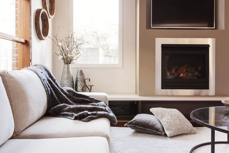 gas fireplace in living room with couch, blankets, pillows, and rug (Photo by © Jodie Johnson - stock.adobe.com)