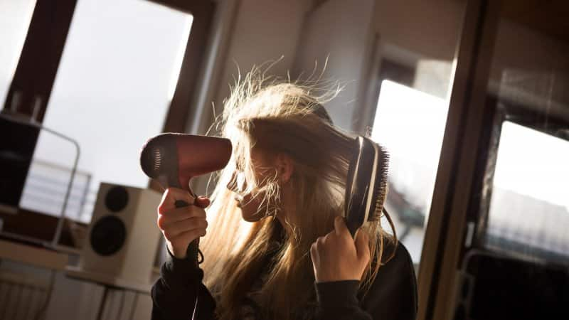 A girl blow drying her hair (Photo by Elva Etienne/Moment via Getty Images)