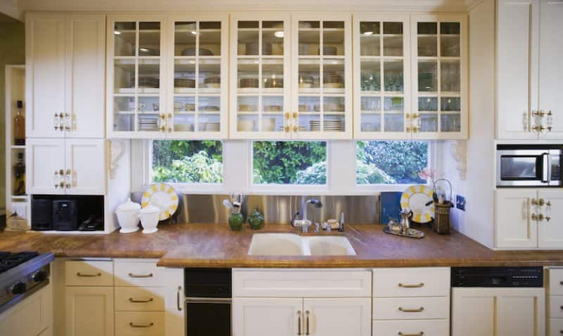 kitchen with windows, wood countertop, and cream cabinets with glass  (Photo by  Andersen Ross/DigitalVision via Getty Images)