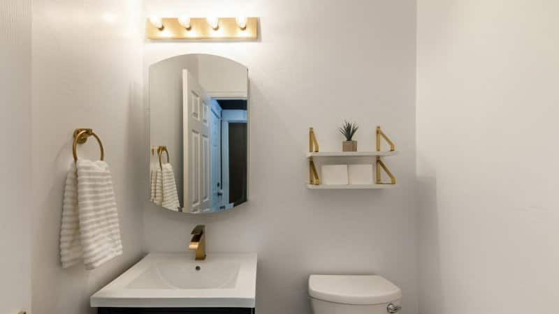 Small powder room with matching gold faucet, towel ring, and open-concept shelf  (Photo by Jason – stock.adobe.com)