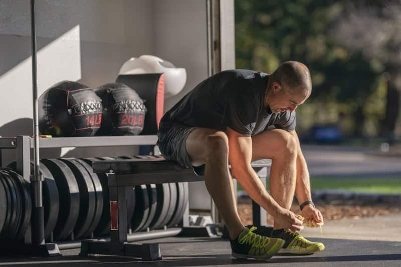 Man in gym clothes lacing up his sneakers in his garage home gym with gym equipment stored behind him (Photo by Fly View Productions / E+ via Getty Images)