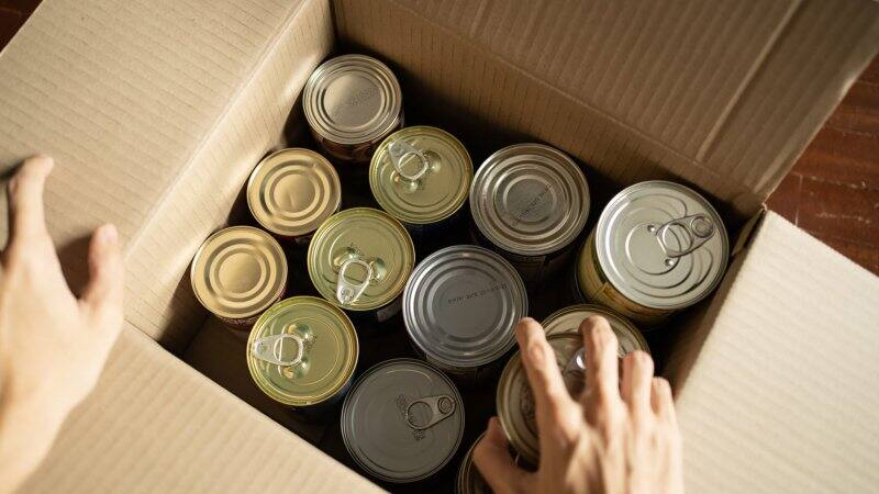 A hand placing canned food in a cardboard box (Photo by Wachiwit/iStock / Getty Images Plus via Getty Images)