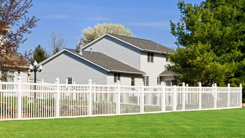 A white vinyl fence enclosing a backyard (Photo by © ghornephoto/Getty Images)