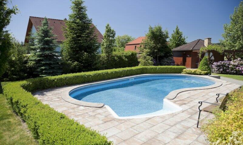 home swimming pool with stone patio and shrubbery and houses in background (Photo by kropic - stock.adobe.com)