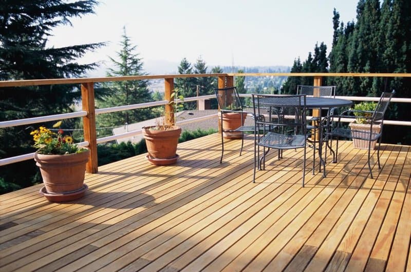 home wood deck with patio furniture overlooking hills with trees (Photo by David Papazian/The Image Bank/Getty Images.)