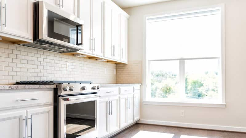 A kitchen interior with a microwave above the gas stove (Photo by Andriy Blokhin - stock.adobe.com)