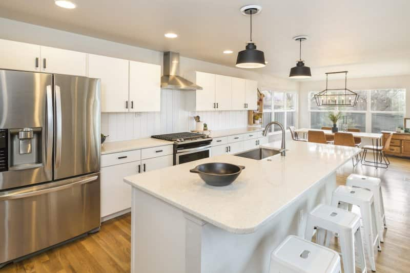 Modern farmhouse kitchen with big center island, white cabinets, countertops and shiplap backsplash, and wood kitchen table (Photo by Neil - stock.adobe.com)