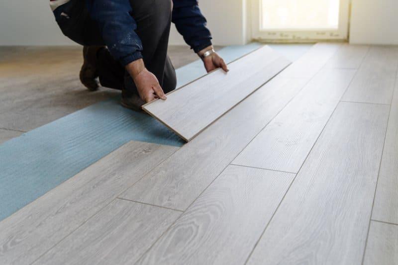 worker installing grayish tan slabs of laminate flooring (Photo by Miljan Živković/iStock/Getty Images Plus via Getty Images)