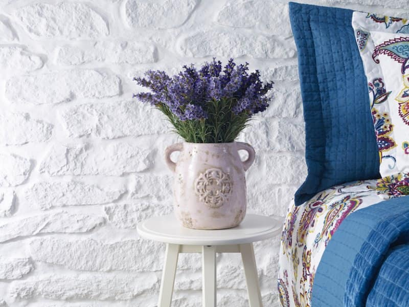 closeup of bunch of lavender in vase on white stool next to colorful bed against white brick wall (Photo by  gerenme/iStock / Getty Images Plus via Getty Images)