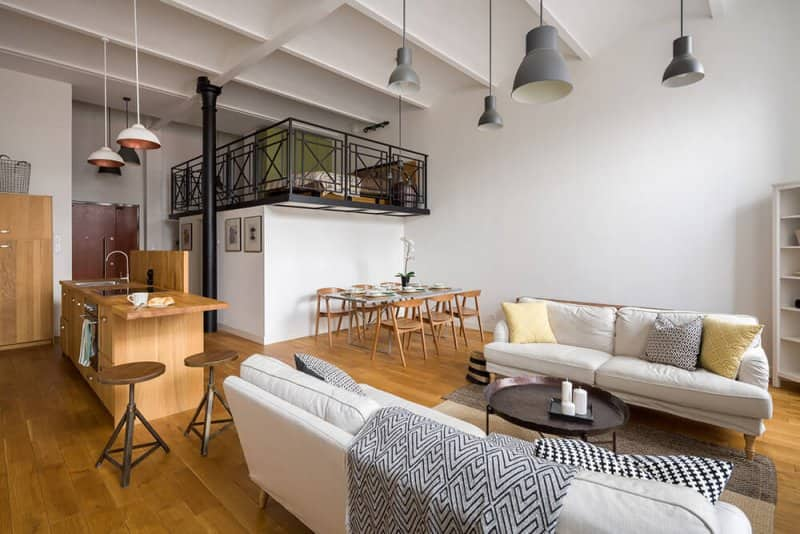 Open living room and kitchen with a loft and wood flooring (Photo by in4mal/iStock/Getty Images Plus/Getty Images)