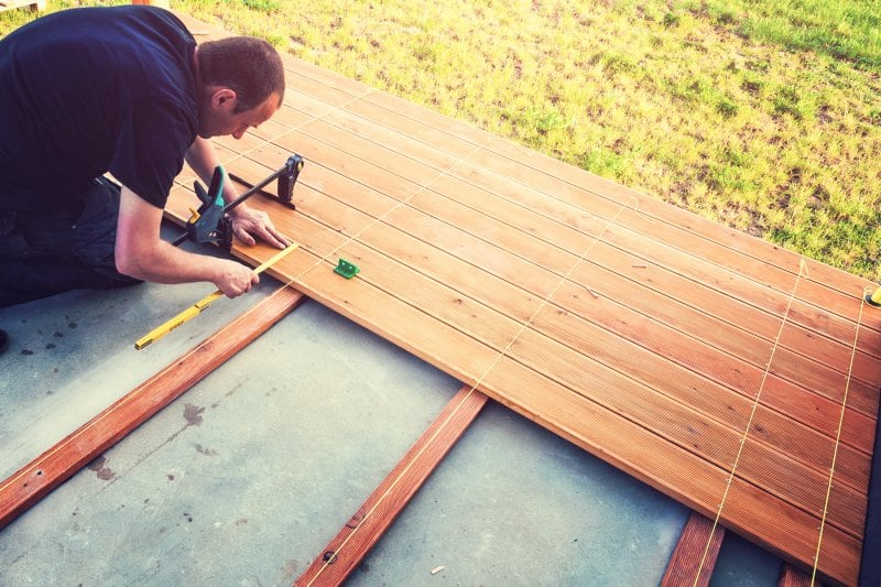 man measuring and building wooden deck (Photo by Avalon_Studio/E+/Getty Images.)