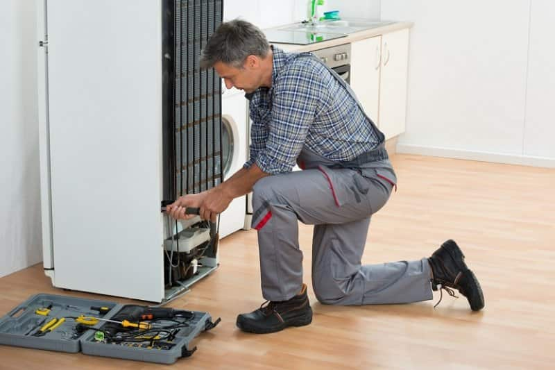 Man repairing refrigerator (Photo by © AndreyPopov / iStock / Getty Images Plus / Getty Images)