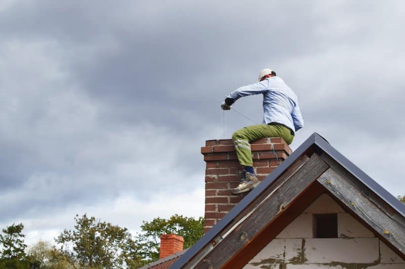 man sweeping chimney on top of house (Photo by © Inga - stock.adobe.com)