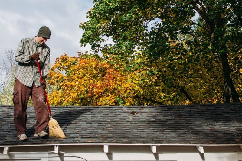 man sweeping leaves on roof (Photo by Deirdre Malfatto/Stocksy - stock.adobe.com)