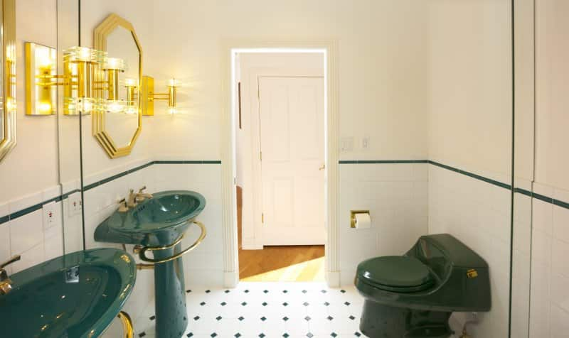 Bathroom with green sink and toilet, gold metal accents, black-and-white tile floors, and a mirror covering the back wall (Photo by James Brey / iStock / Getty Images Plus via Getty Images)