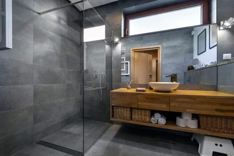 Modern bathroom with large dark tile and wood counter (Photo by Jacek Kadaj/Moment/Getty Images)