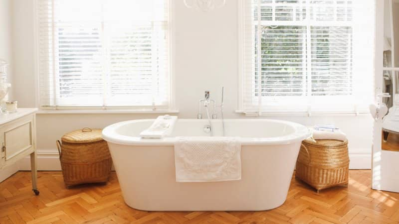 A modern bathtub in a sunlit bathroom (Photo by Daly and Newton/OJO Images via Getty Images)