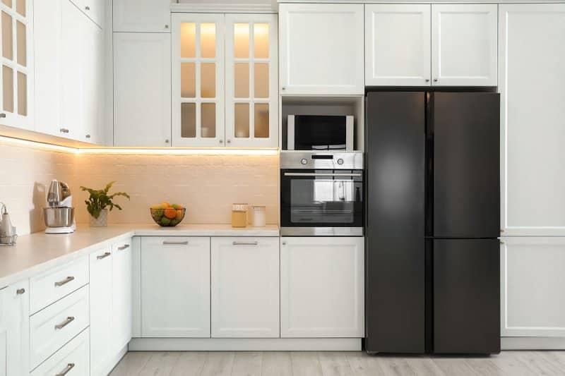 white kitchen decor with sleek black fridge (Photo by New Africa - stock.adobe.com)