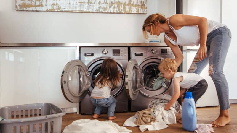 A mom with her children loading the washing machine with clothes (Photo by jacoblund/iStock/Getty Images Plus via Getty Images)