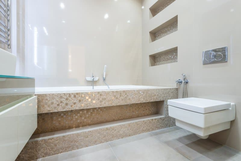 Bathroom with brown mosaic tile tub, wall-hung toilet, and built-in mosaic shower shelves (Photo by Max Vakhtbovych from Pexels)