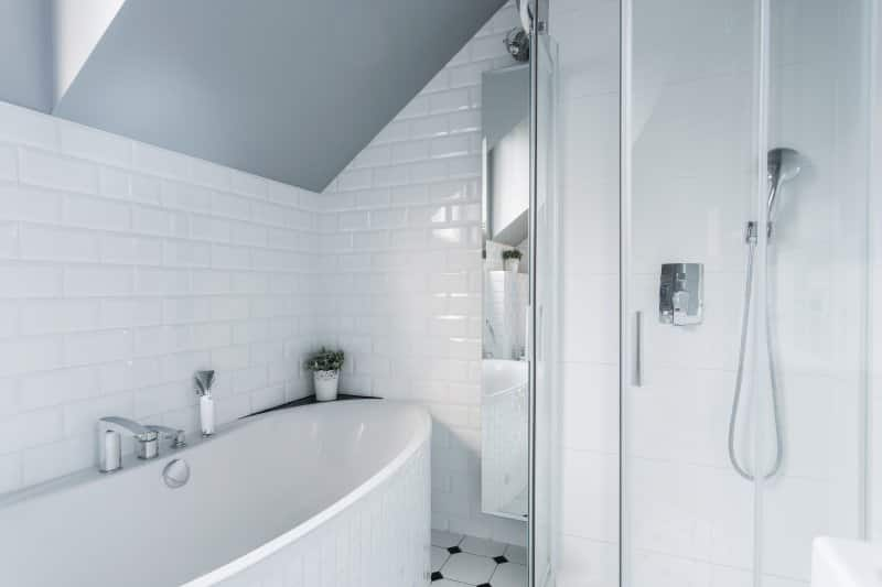 Separate bathtub and shower in white-tile bathroom (Photo by Photographee.eu – stock.adobe.com)