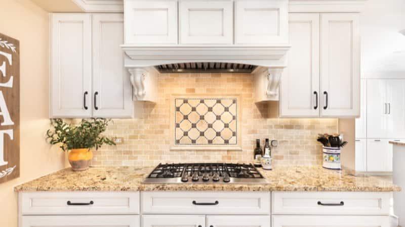 Tan natural stone backsplash and kitchen stove (Photo by Joe Hendrickson/Shutterstock.com)