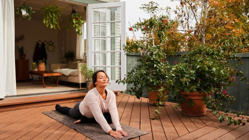 woman practicing yoga with her eyes closed on her patio (Photo by  Goodboy Picture Company / E+ via Getty Images)