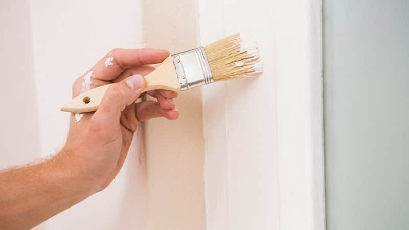 Painting trim white next to a blue wall (Photo by Wavebreakmedia/ iStock / Getty Images Plus via Getty Images)
