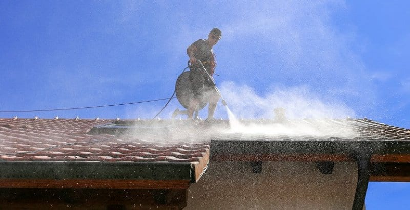professional roof washer power washing (Photo by  Marina Lohrbach / IStock / Getty Images Plus)
