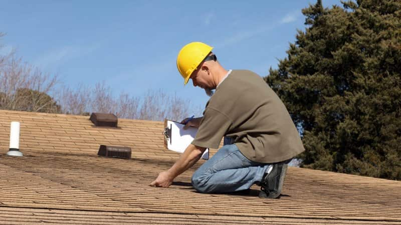 A professional inspecting a house's roof (Photo by Imagesbybarbara/E+ via Getty Images)