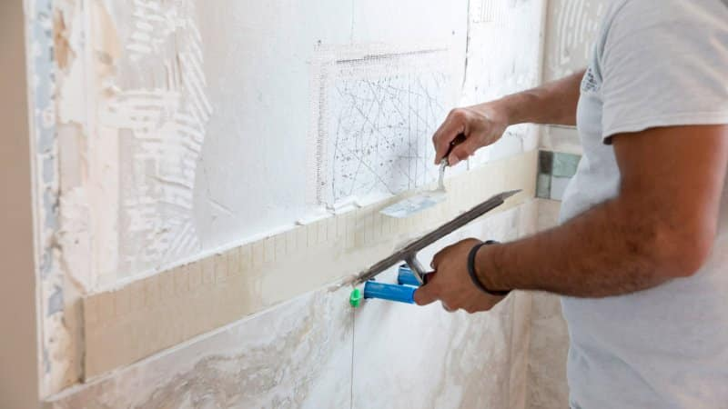 A professional laying new tiles in a shower (Photo by Jodi Jacobson/E+ via Getty Images)