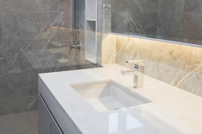 a white quartz bathroom countertop with rectangular shapes, silver fixtures, and tan and gray marbled walls (Photo by nongnuch_l - stock.adobe.com.)