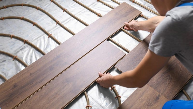 Contractor lays flooring over radiant heat (Photo by By New Africa - stock.adobe.com)