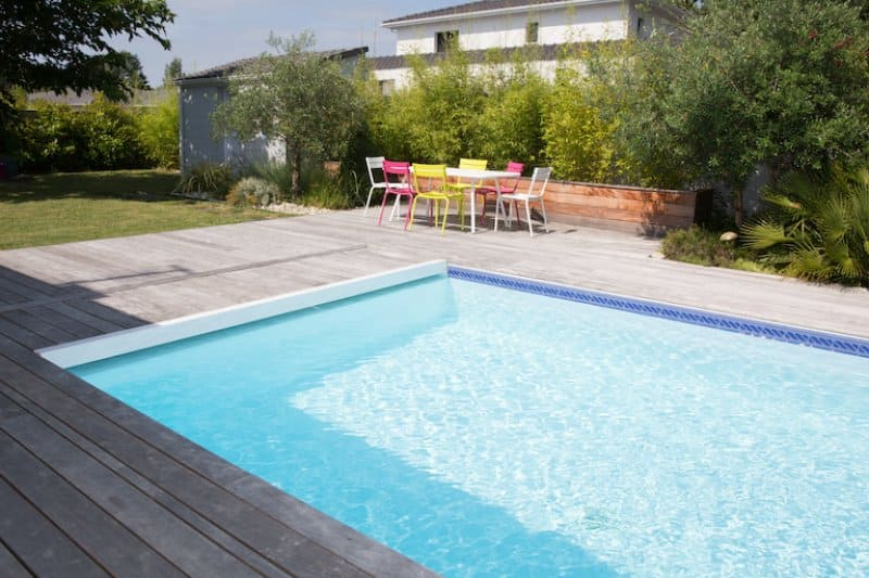 partial view of rectangular pool with concrete patio area and colorful patio furniture in background (Photo by OceanProd - stock.adobe.com)