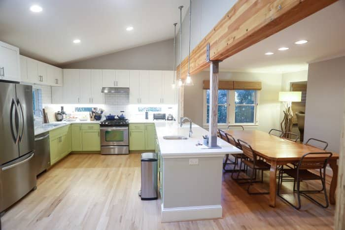 open kitchen with white subway tile and exposed wood