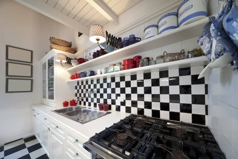 Kitchen with black-and-white checked tile backsplash, white cabinets, and retro tins on white open shelves (Photo by Javani LLC - stock.adobe.com)