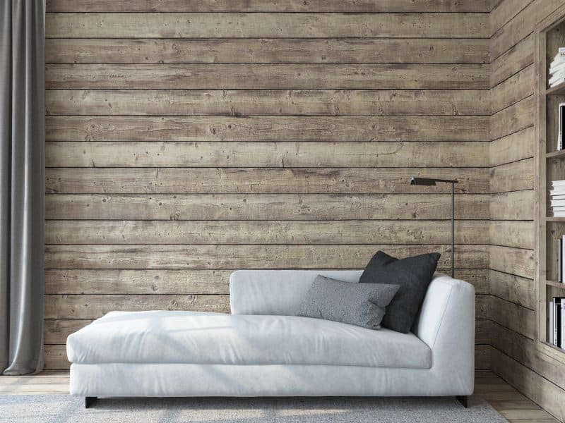 Living room with a gray couch in front of rustic wood shiplap walls and built-in bookshelves (Photo by poligonchik - stock.adobe.com)