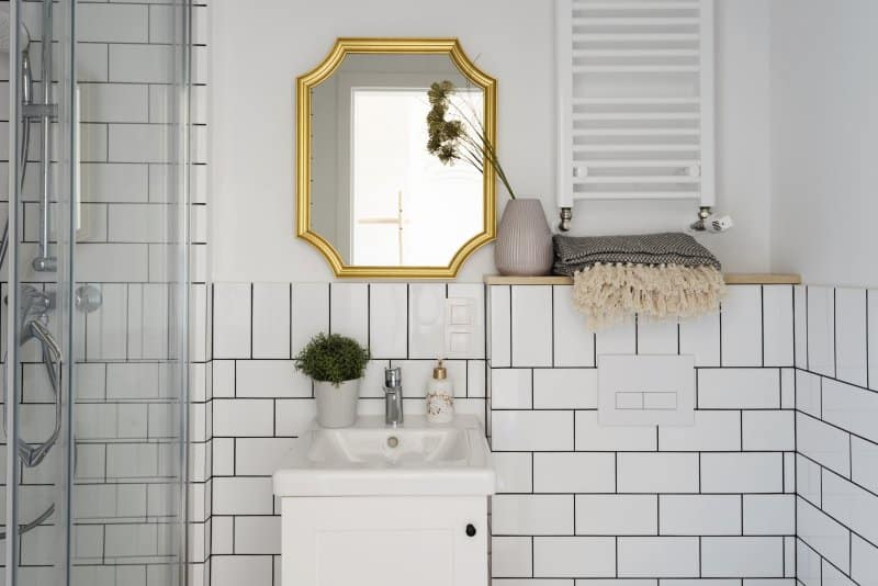 Small bathroom with white subway tiles, bathroom sink and stylish gold mirror on the wall (Photo by photosbysabkapl – stock.adobe.com)