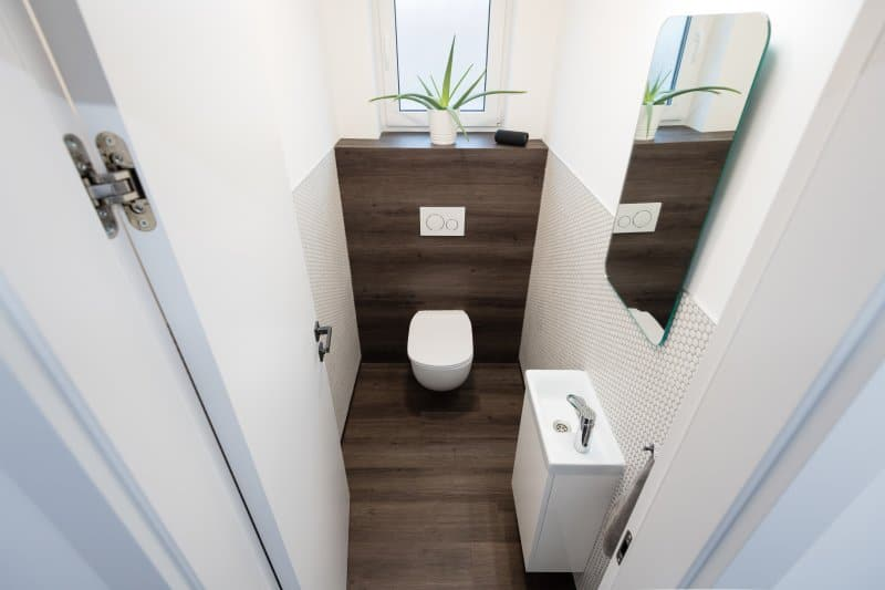 Tiny apartment bathroom bathroom with wood floor and accent wall, wall-hung toilet, honeycomb tiles, and rectangular sink (Photo by ventura – stock.adobe.com)