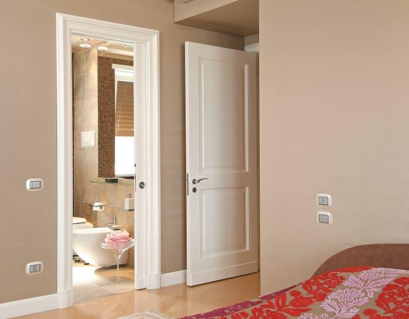 Beige bedroom with ensuite bathroom and open pocket door (Photo by #moreideas – stock.adobe.com)