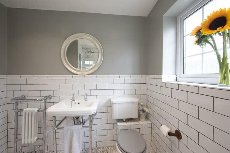 Industrial vessel bathroom sink on wood vanity below industrial pendant lamp and three mirrors (Photo by John Keeble / Moment via Getty Images)