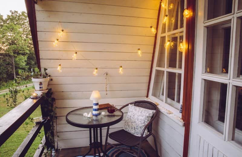 small patio with round coffee table and chair, with string lights hanging from ceiling (Photo by FotoHelin - stock.adobe.com)