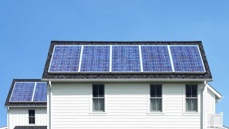 solar panels roof white house (Photo by Steven Puetzer/The Image Bank via Getty Images)