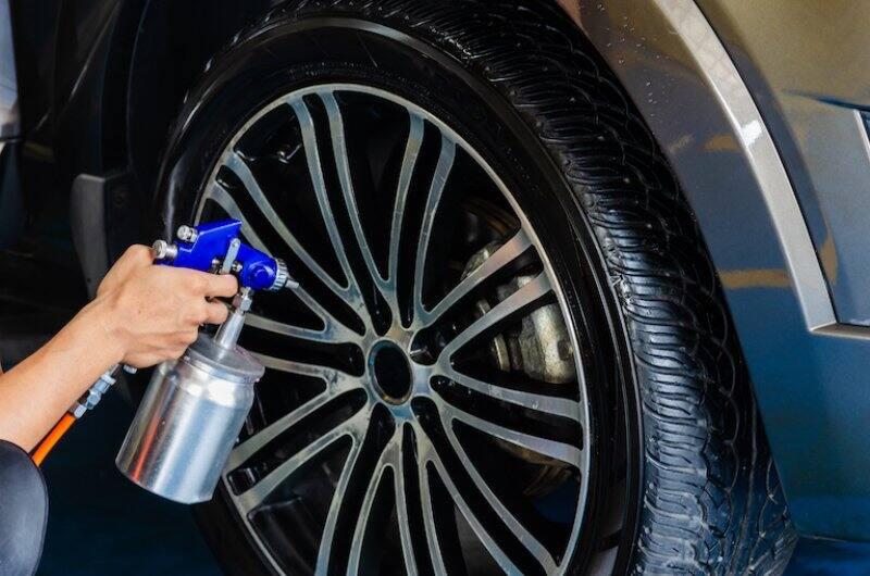 hands holding spray coating, spraying car wheel (Photo by khunkorn - stock.adobe.com)